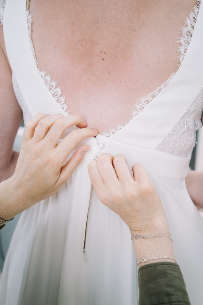 White dress with laces and an open back - Preparation of the bride - Wedding photography in Berlin
